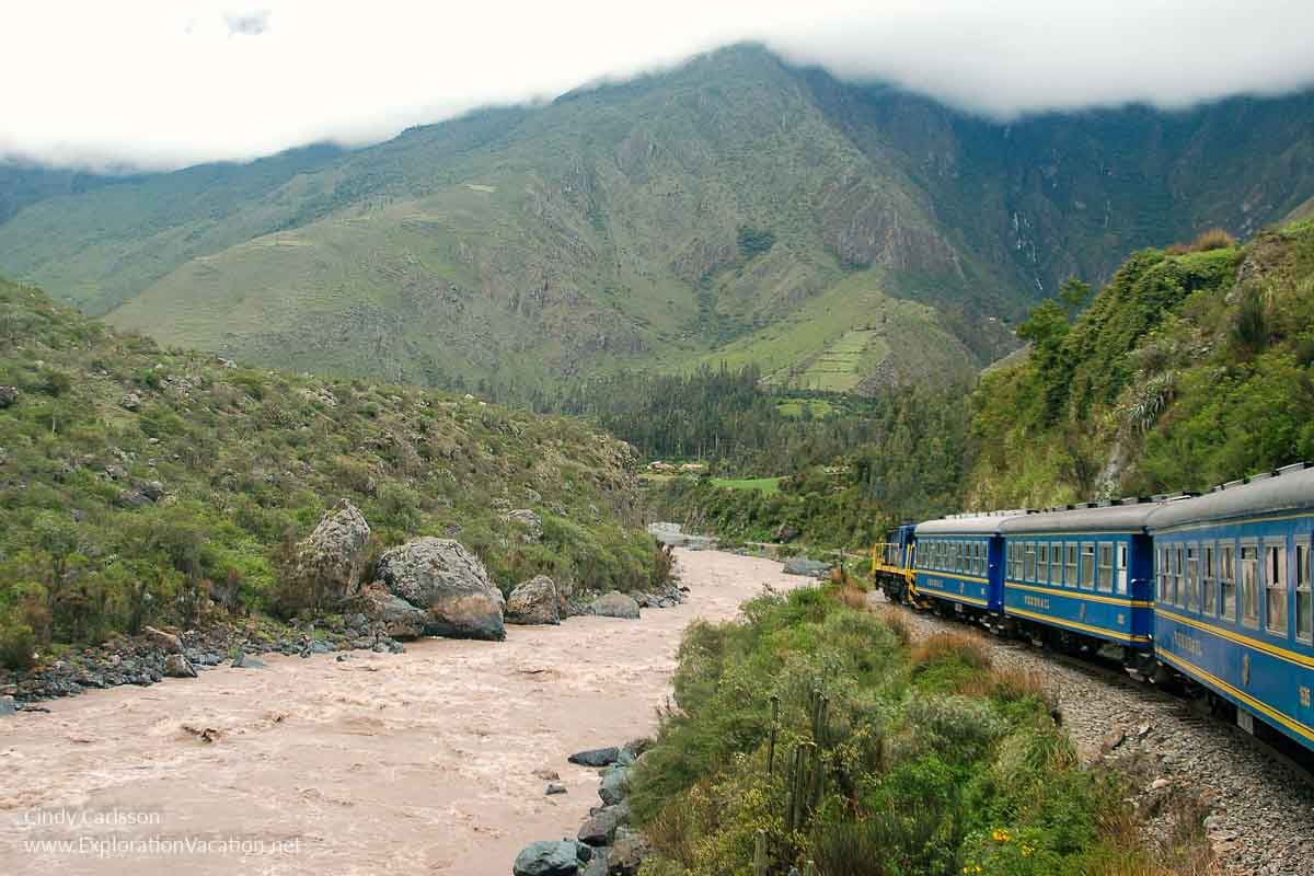 passenger train along a river through the mountains
