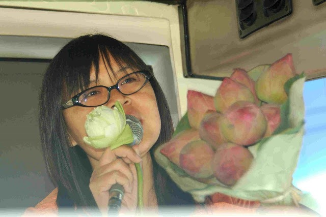 woman with microphone and bouquet of lotus buds