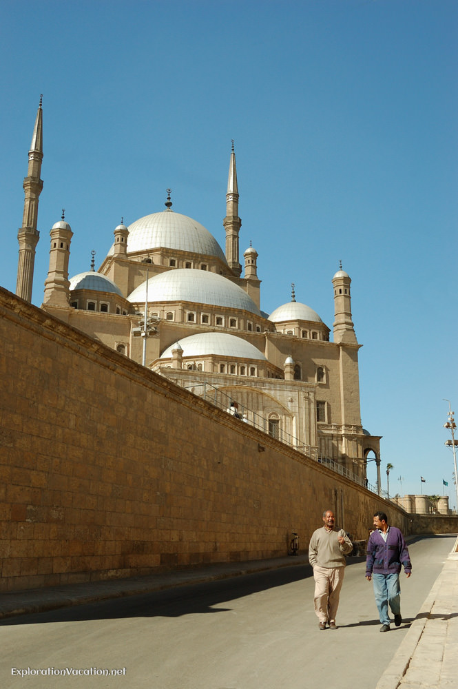 multiple domes and minarets rise above a wall along the sidewalk