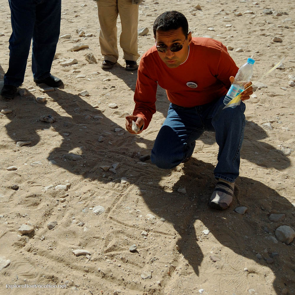 man drawing diagrams in the sand