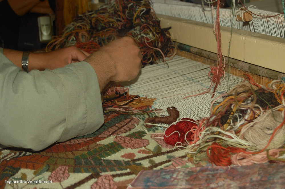 detail of hands weaving a carpet