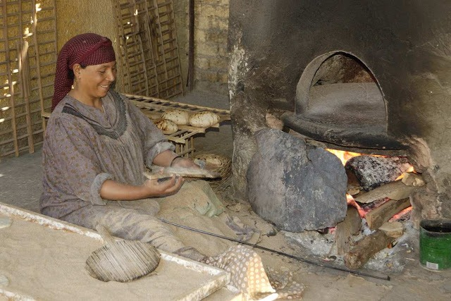 woman baking bread in a traditional oven