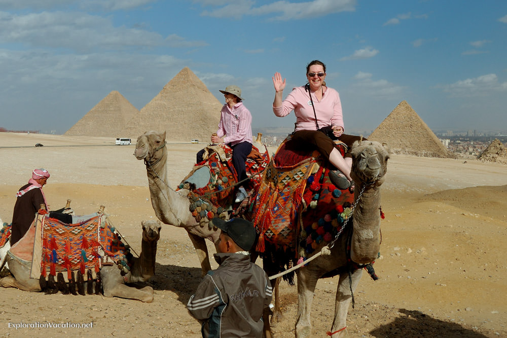 people on camels with pyramids in the background