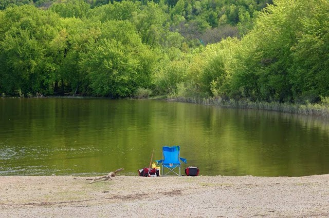 lawn chair, fishing poles, buckets, and other gear set up along the river bank