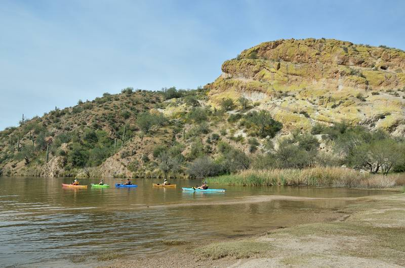 kayaks in the water below the bluff
