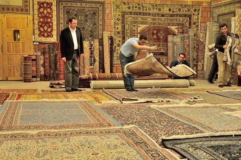 rug shop with a man flipping a carpet