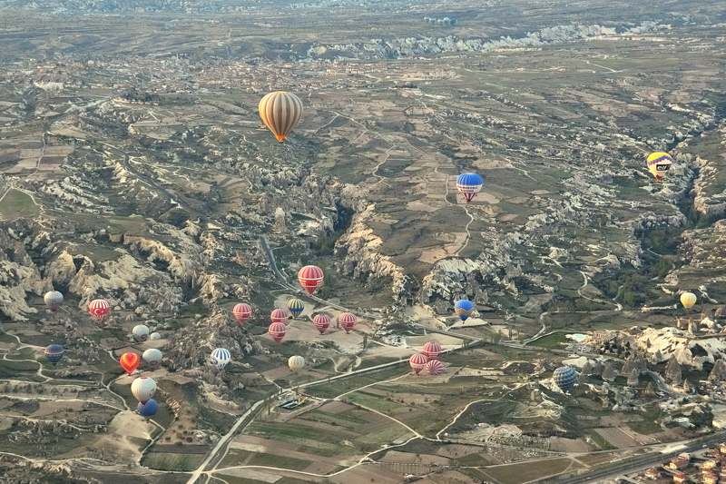 Balloons over a rugged landscape