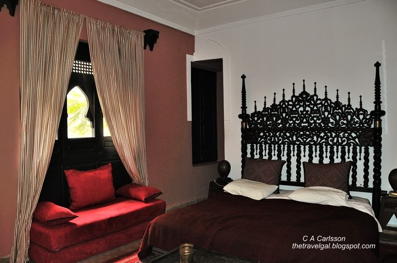room with a large window and ornate bedframe