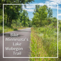 "paved trail through woods and meadow with text ""Bike Minnesota's Lake Wobegon Trail"""