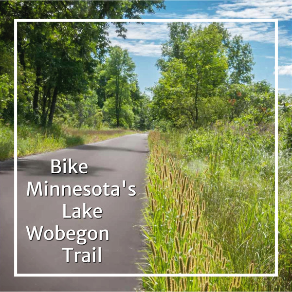 """paved trail through woods and meadow with text """"Bike Minnesota's Lake Wobegon Trail"""""""