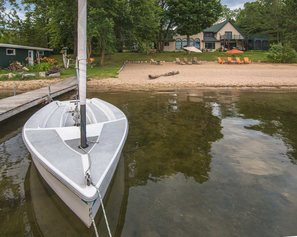 sailboat along a beach with a lake home B&B in the background