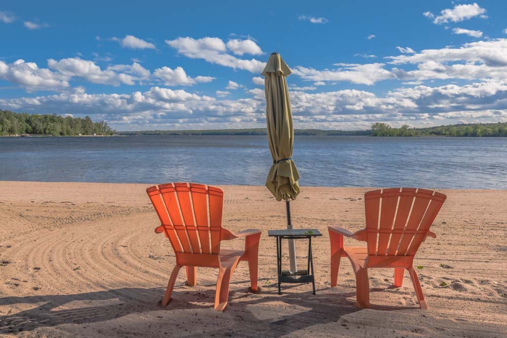 orange plastic chairs and closed umbrella on beach by a lake