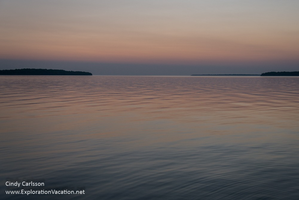 pink and purple dawn reflected on water with islands on the horizon