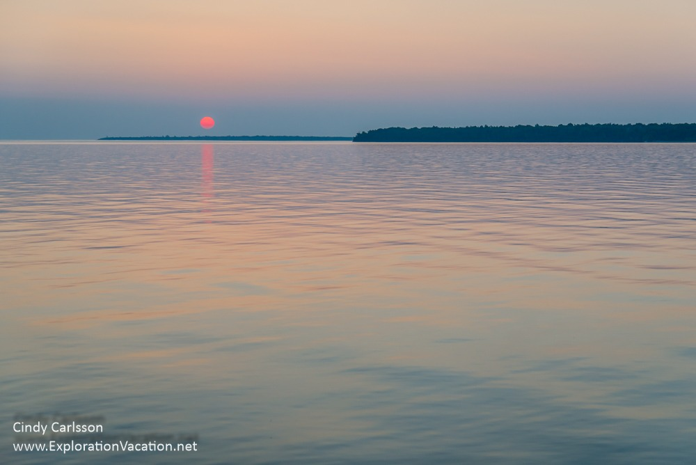 pastel reflections on the water with bright red sun just above the horizon