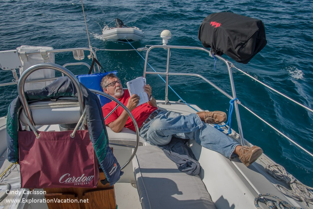 Man reading while relaxing at the back of a sailboat