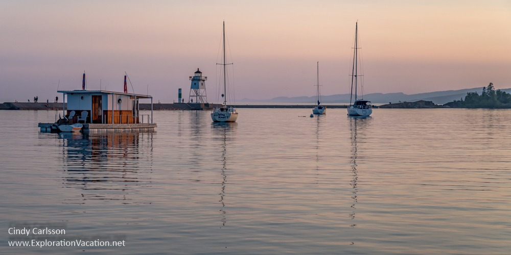 boats and lighthouse at dusk