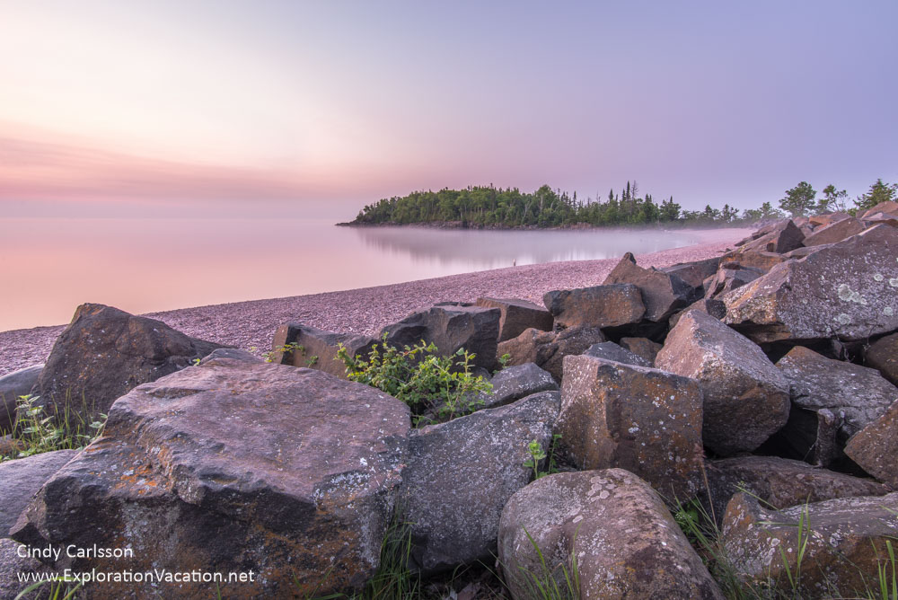 shoreline with large boulders and pink and purple sky and water