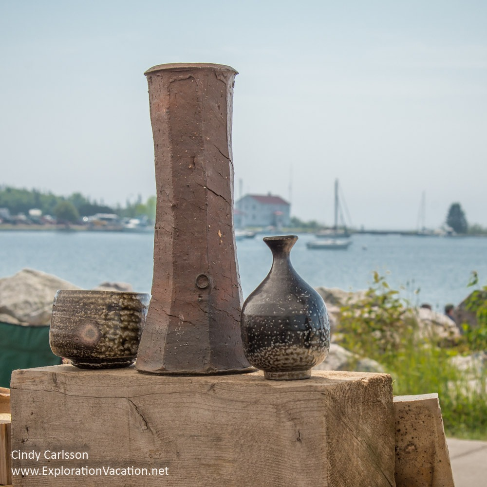 three pieces of pottery on display with a harbor visible in the background