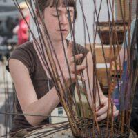 artist working on a basket