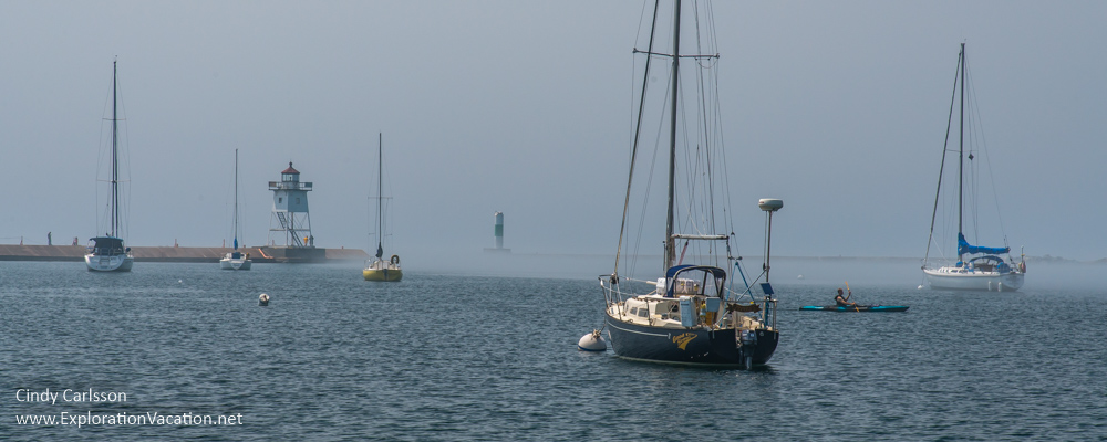sailboats and lighthouse in light fog