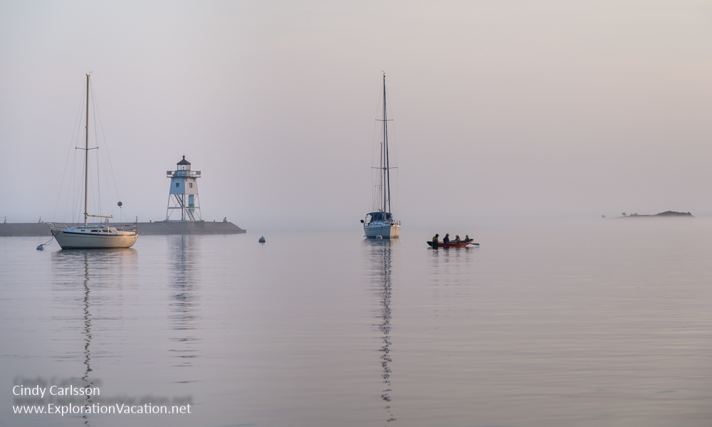 lighthouse and sailboats on a still evening with sea smoke