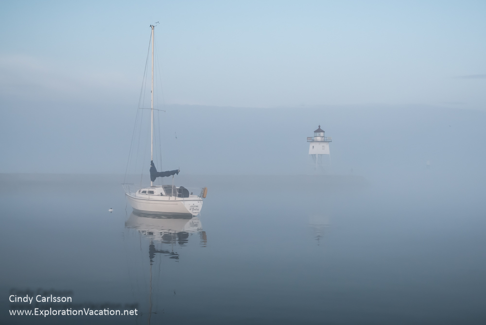 sailboat and lighthouse in fog