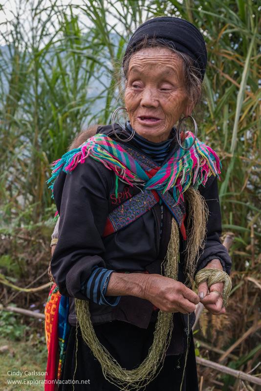 Hmong woman twisting thread Vietnam road trip Black Hmong village Sapa - ExplorationVacation
