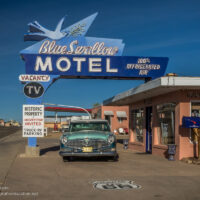 Blue Swallow Motel sign over a classic car outside an old motel