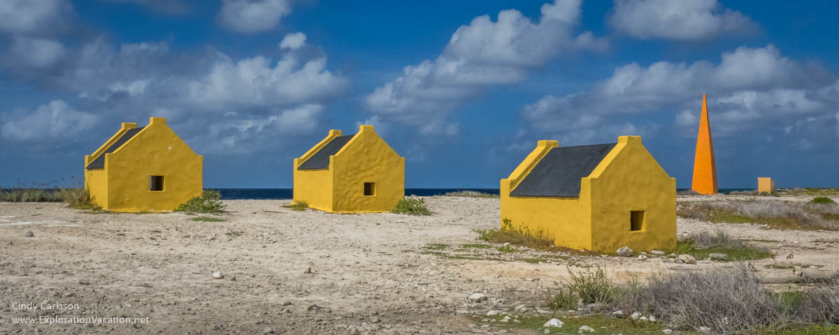 yellow stone shacks along a beach