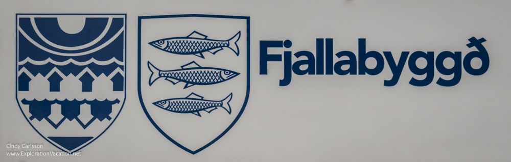 sign with coat of arms of the two cities that form Fjallabyggð