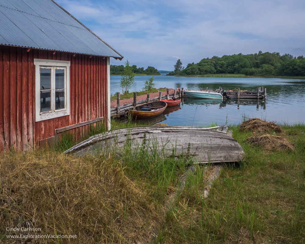 red wood boathouse with old boat on land and boats in the bay