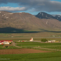 farmsteads and church below the mountains