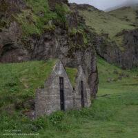 run-down turf houses below a mountain