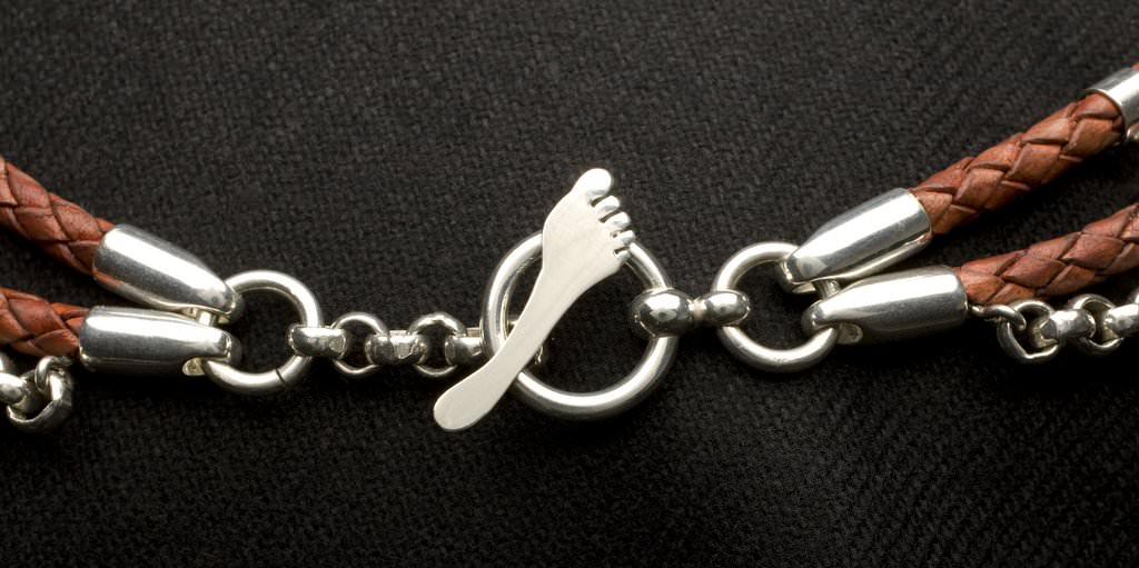 silver charm of a bare foot used as a necklace clasp