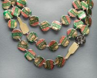 detail of a necklace made of Moosehead bottle caps and brass images of beer bottles
