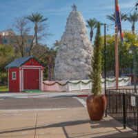 street scene with red shed and large white Christmas tree
