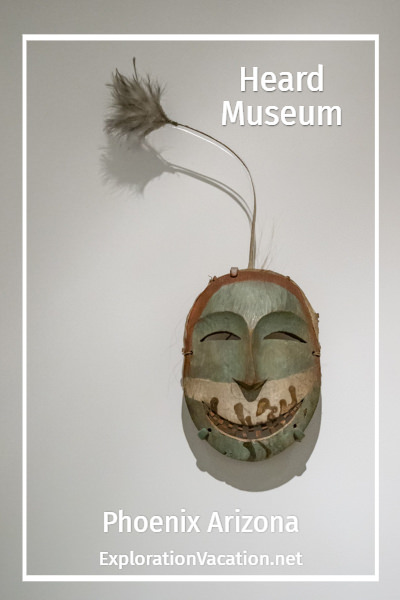 carved wooden mask with text