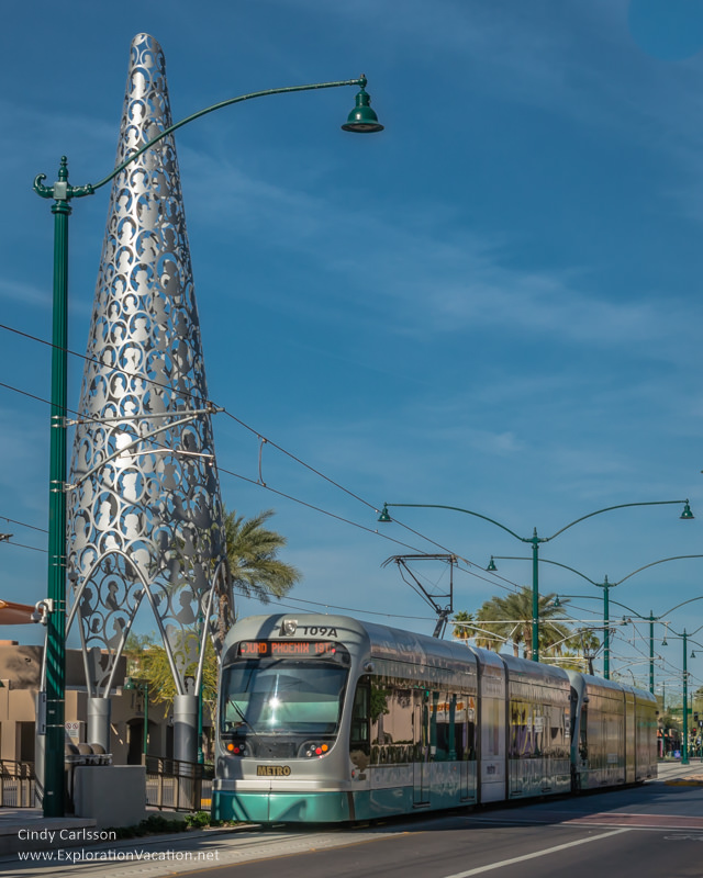 light rail train passing by a tall pine tree-shaped sculpture in Mesa Arizona