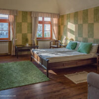 Hotel room with green and white walls, bed, and large windows