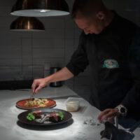 chef preparing two plates in the kitchen