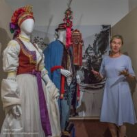 The museum curator with folk costumes in a museum