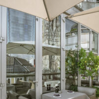 Restaurant patio with cathedral reflected in windows