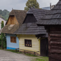 Colorful log homes along a narrow road