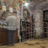 cave-like interior of the wine shop with a ghosted figure at the counter and racks of wine bottles