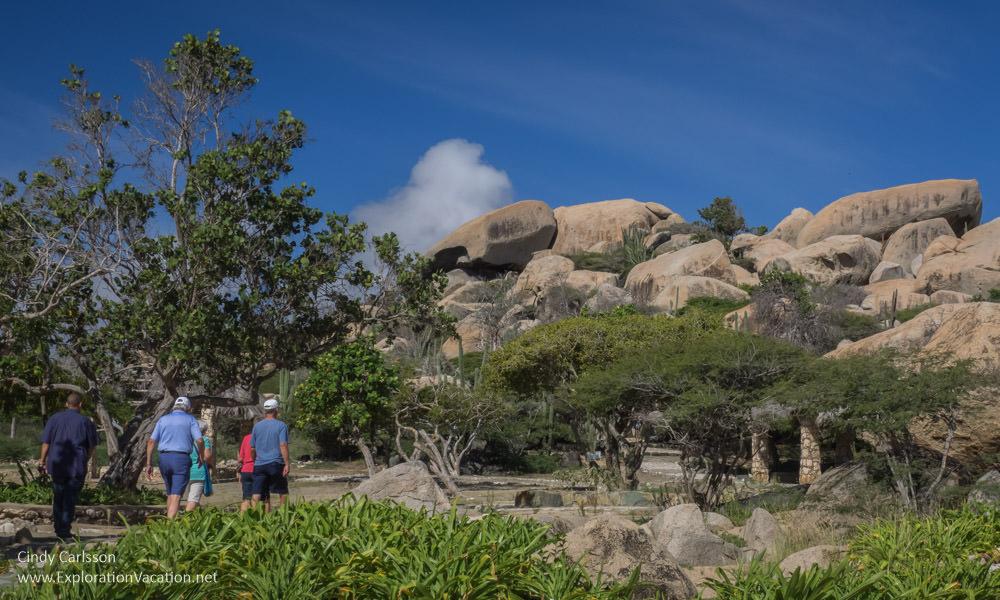 hikers walking toward a large rock formation