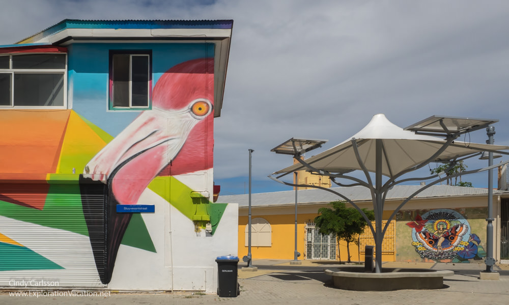 flamingo painted on a building with another mural in the background