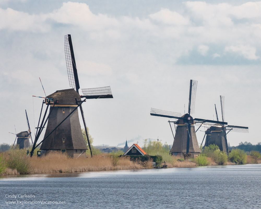 row of windmills along a canal