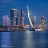 evening picture of illuminated cable-stayed bridge and buildings