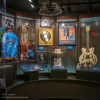 exhibit in the museum with clothing, records, awards, a guitar, and more