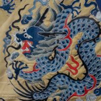blue dragon embroidered on a gold fabric